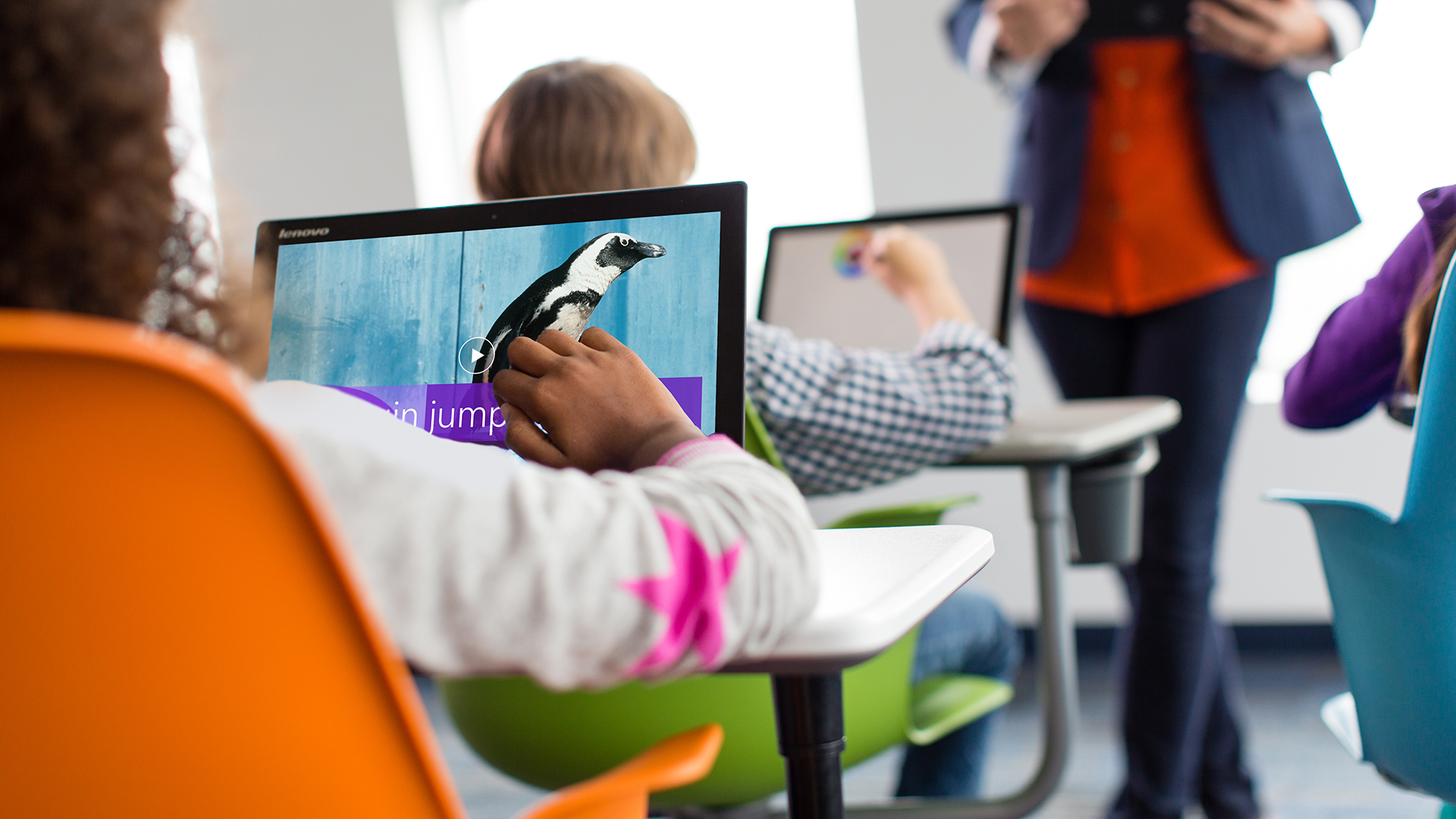 A child using a microsoft interface in a classroom environment to get creative.